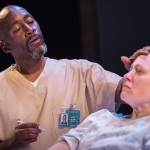 Photo Credit: Owen Carey for Artists Repertory Theater. Victor Mack plays a nurse comforting Lanie (Dana Millican).